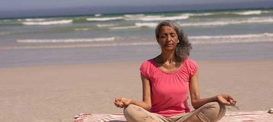 Femme sur la plage faisant du yoga